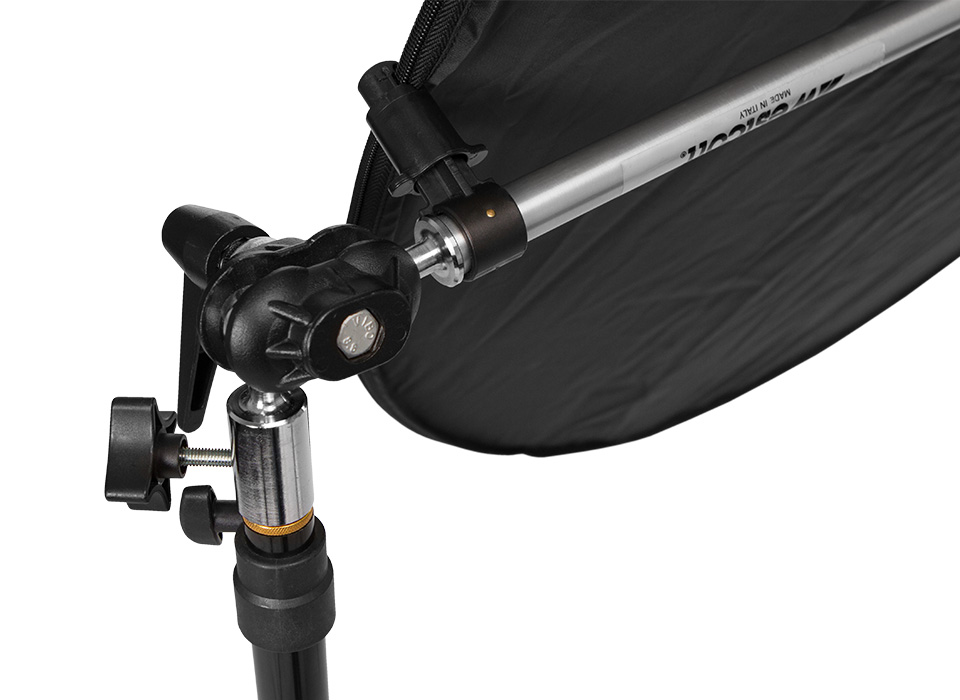 Illuminator reflector arm with metal construction and tilting ball joint