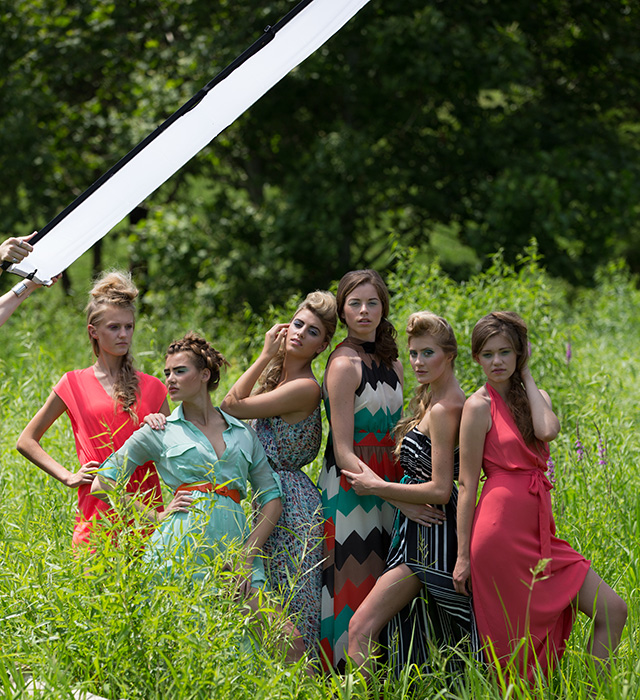 Group of models being photographed outdoors with sunlight softened by Scrim Jim Cine diffusion fabric