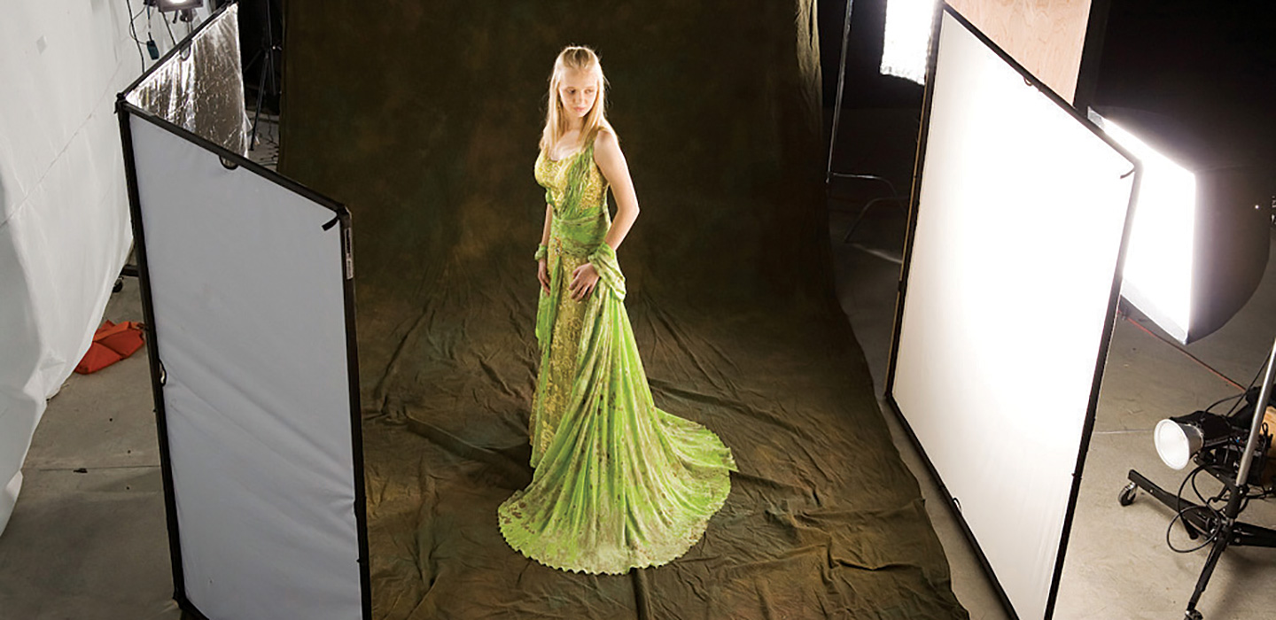 Studio photography setup with female model being photographed using a brown hand-painted muslin backdrop