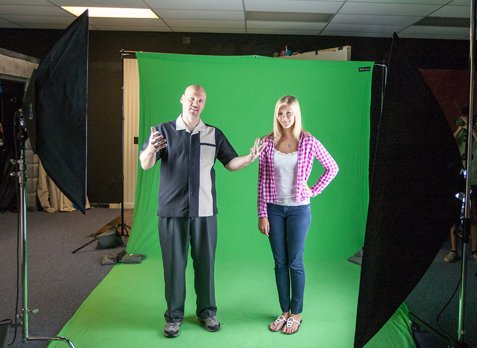 Photography studio with green screen backdrop mounted with backdrop support system