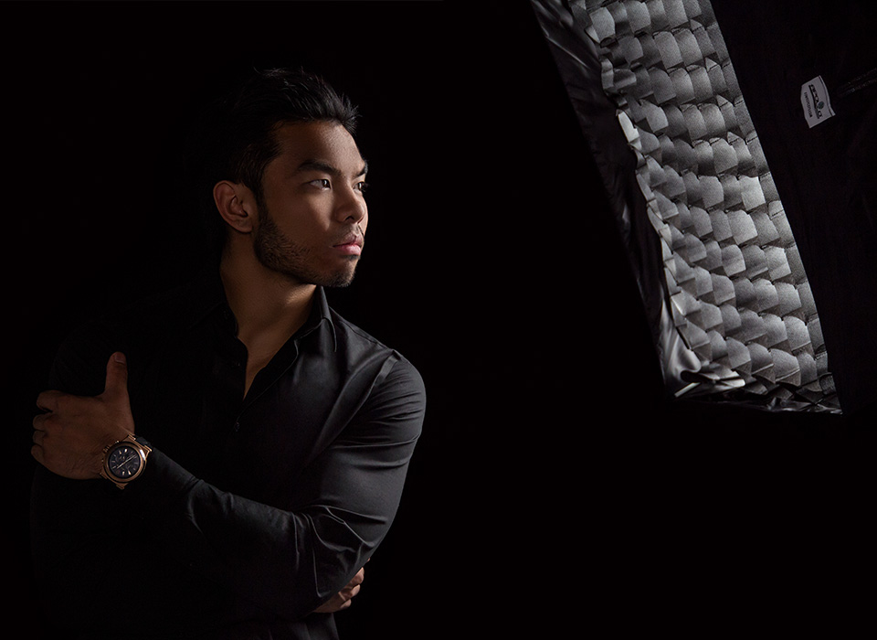 Photo studio lighting setup with strip softbox light modifiers and black collapsible backdrop